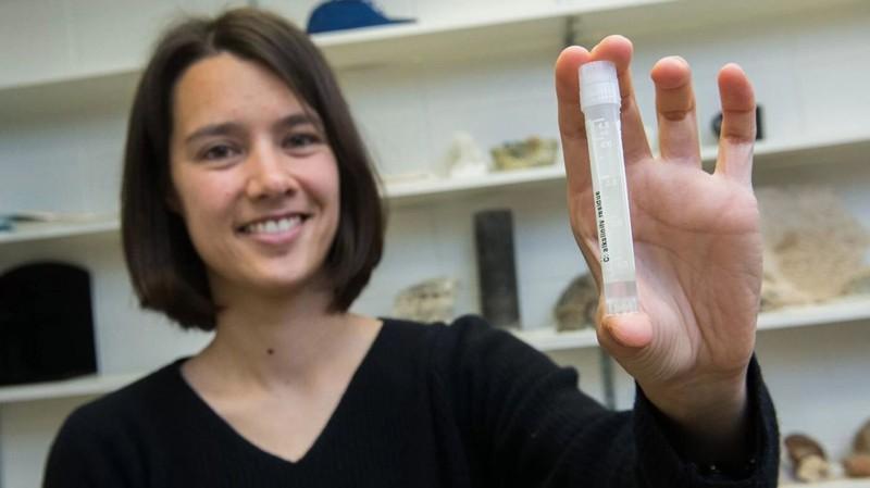 La profesora asistente Clara Blättler con un frasco de agua de mar que data de la última Edad de Hielo, hace aproximadamente 20.000 años