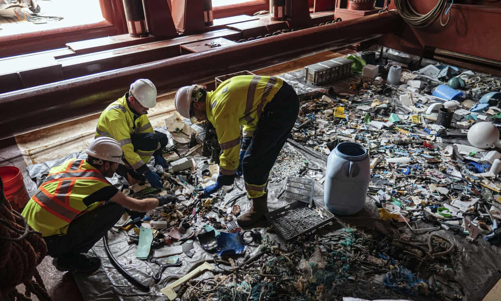 Los miembros de la tripulación clasifican el plástico a bordo de una embarcación de apoyo en el Pacífico