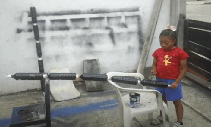 Xóchitl cubre una serie de botellas de agua conectadas con pintura negra mientras construye su calentador de agua